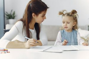 woman-teaching-little-kid-how-to-draw-3985026